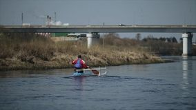 Disabled man rowing on the river in a canoe. Rowing, canoeing, paddling. Training. Kayaking. paraolympic sport. Bridge. Disabled Athlete rowing on the river in a stock video footage