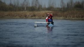 Disabled man rowing on the river in a canoe. Rowing, canoeing, paddling. Training. Kayaking. paraolympic sport. Slow. Disabled Athlete rowing on the river in a stock footage