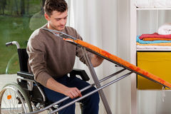 Disabled man setting up an iron board Stock Photos