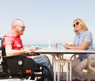 Disabled man sits with a woman stock images