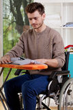A disabled man sitting and ironing shirt Stock Photo