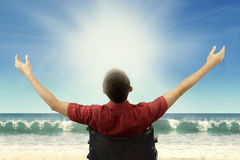 Disabled man sitting on weelchair at beach. Rear view of disabled young man enjoy freedom while sitting on wheelchair and raise hands up at beach Royalty Free Stock Photo