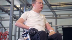 A disabled man is sitting in a wheelchair with dumb-bells, moving his shoulders and talking. 4K stock footage