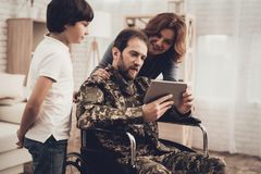 Disabled Man Soldier Watch A Tablet With Family. Disabled Man In A Wheelchair Watch A Tablet With Family. Meeting After War. Son And Wife. Camouflage Uniform stock photography