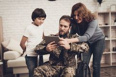 Disabled Man Soldier Watch A Tablet With Family. Disabled Man In A Wheelchair Watch A Tablet With Family. Meeting After War. Son And Wife. Camouflage Uniform stock photo
