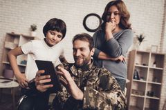 Disabled Man Soldier Watch A Tablet With Family. Disabled Man In A Wheelchair Watch A Tablet With Family. Meeting After War. Son And Wife. Camouflage Uniform stock image