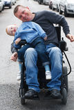 Disabled man with son on wheelchair Stock Photos