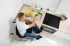 Disabled man with sponge washing dishes Royalty Free Stock Image