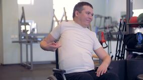 A disabled man is stretching his arms and shoulders while sitting in a wheelchair stock footage
