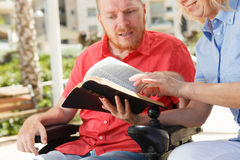 Disabled man studying Holy Bible. We studying Holy Bible together. Disabled man Royalty Free Stock Photo