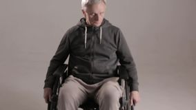 Disabled man suffering from loneliness. Sitting In Wheelchair And Looking Down. Disability Concept stock video