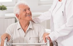 Disabled man and supporting physiotherapist Royalty Free Stock Photos