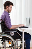 Disabled man surfing on the Internet Stock Photo