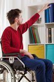 Disabled man taking book Stock Photography