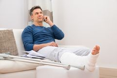 Disabled man talking on cellphone. Man With Fractured Leg Sitting On Sofa Talking On Cellphone Royalty Free Stock Photo