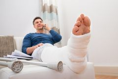 Disabled man talking on cellphone. Man With Fractured Leg Sitting On Sofa Talking On Cellphone Royalty Free Stock Photos