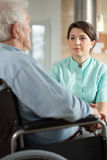 Disabled man talking with nurse Stock Image