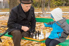 Disabled man teaching his grandson to play chess Stock Images
