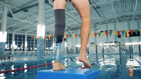 Disabled man training at a pool, bionic leg prosthesis. 4K stock video footage