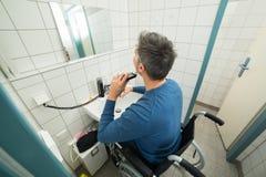 Disabled man trimming beard Stock Photo