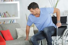 Disabled man trying to sit on couch Royalty Free Stock Images