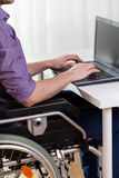Disabled man typing on notebook Royalty Free Stock Photo