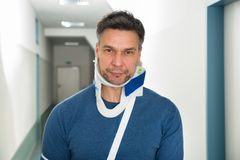 Disabled man using cervical collar. Disabled Man Suffering From Neck Ache Using Cervical Collar royalty free stock photos