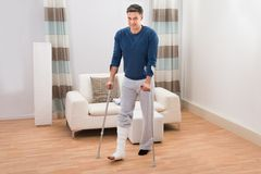 Disabled man using crutches for walking Royalty Free Stock Photography