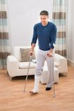 Disabled man using crutches for walking Stock Image