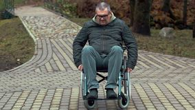 Disabled man using wheelchair on path at outdoor stock video footage