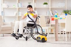The disabled man with vacuum cleaner at home Royalty Free Stock Photography