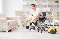 The disabled man with vacuum cleaner at home Royalty Free Stock Image
