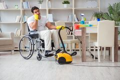 The disabled man with vacuum cleaner at home Stock Image