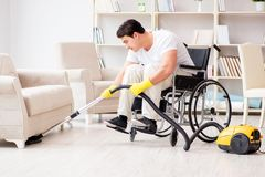 The disabled man with vacuum cleaner at home Stock Photography