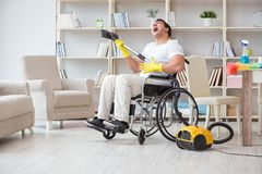 The disabled man with vacuum cleaner at home Stock Photo