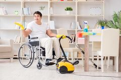 The disabled man with vacuum cleaner at home Stock Images
