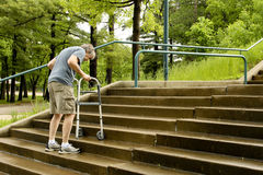 Disabled man with a walker. Elderly man climbs the stairs outdoors with the help of a walker Royalty Free Stock Photography
