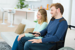 Disabled man watching TV with girlfriend Stock Photography