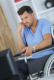 Disabled man watching tv in living room at home. Disabled man watching tv in the living room at home Stock Image