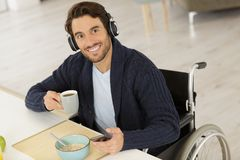 Disabled man wearing headset holding coffe. Coffee stock image