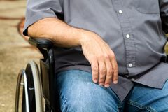 Disabled Man In Wheelchair. Close up of disabled man's arm and torso as he sits in a wheelchair Royalty Free Stock Photo