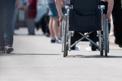 Disabled man on wheelchair. Disabled (handicapped) person on wheeled chair among people without disabilities. Place for copy Royalty Free Stock Photography