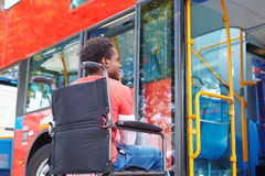 Disabled Man In Wheelchair Boarding Bus. By Himself Struggling Royalty Free Stock Photography