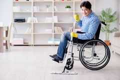 The disabled man on wheelchair cleaning home Stock Photo