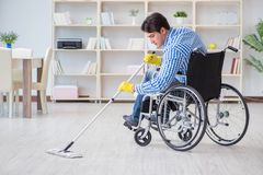 The disabled man on wheelchair cleaning home Stock Image