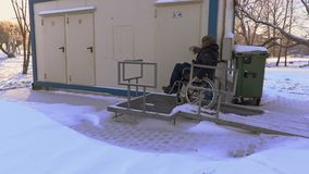 Disabled man on wheelchair drive near to public toilet. In winter  day stock footage