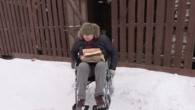 Disabled man on wheelchair with firewood logs near the barn stock footage