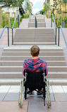 Disabled man in wheelchair in front of stairs Royalty Free Stock Images