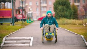 Disabled man in wheelchair going down the ramp outdoors