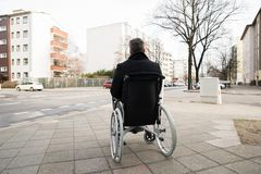 Disabled man on wheelchair looking at street Stock Photos